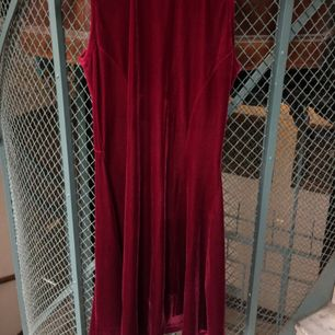 Röd sammetsklänning med knäppning i ryggen och en Cut out vid ryggen. Polo detalj, kort klockkjol. I stretch som sitter tajt och snyggt! Säljer för att den inte kommit till användning