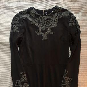 svart klänning med coola broderier vid halsringning och ärmslut. köpt på emmaus vintage och aldrig använd av mig, fint skick. lapp med märke och storlek saknas men uppskattar den till en storlek S