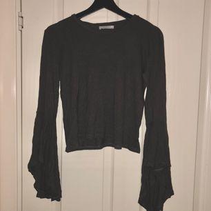 Mörkgrå tröja mes volangärmar. I väldigt gott skick. Köpare betalar frakt.