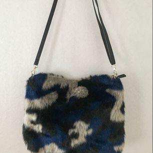 🍭 axelremsväska från Monki, köpt för några år sedan och sparsamt använd. I fuskpäls med camouflage-mönster💙 bredd: 25cm höjd: 20cm