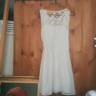 Superfin, knappt använd vit klänning. V-ringning i spets på rygfen och insydd vid midjan. Kort.