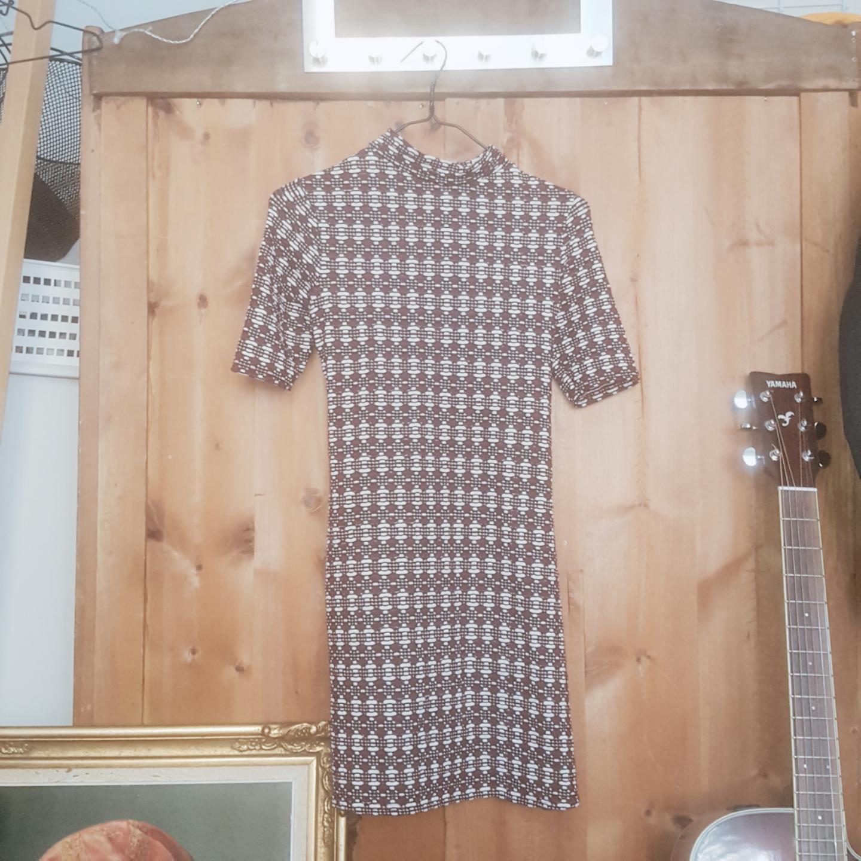 Kort, 60talsinspirerad klänning i röd/brunt mönster. Töjigt, bekvämt tyg och en halvt öppen rygg. Nyskick.. Klänningar.