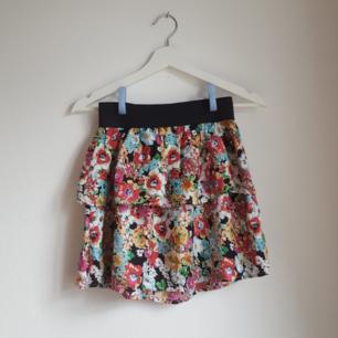 Kort blommig kjol i storlek 36. (S/XS) Köpt på loppis men aldrig använd.