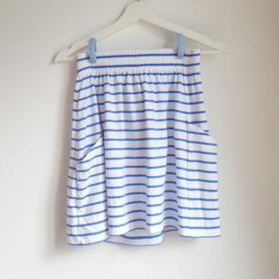 Vit kjol med ljusblå ränder, resår i midjan och två fickor framtill. Aldrig använd.