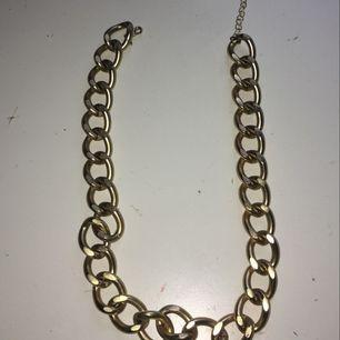 Ett guldigt kedjehalsband som aldrig har användts