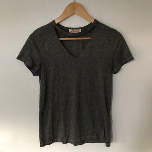 """Grå t-shirt med öppen """"krage"""" från Hollister. Sparsamt använd. 80kr köparen står för frakt 💘"""