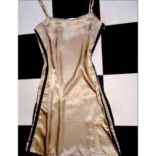 Miniklänning från Omighty, champagnefärgad med två svarta streck på sidan. Aldrig använd, endast provad hemma. Lappen kvar. Måste tyvärr sälja då den var för liten/inte satt bra på mig. Den är M, men känns snarare som en liten S.