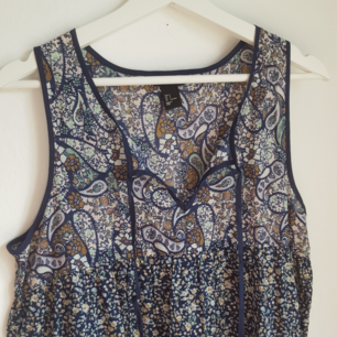 Blommig/mönstrad klänning i blått/grönt. Väldigt tunn i tyget, två fickor framtill och snörning i urringningen. Aldrig använd!
