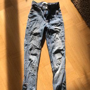 Molly jeans från gina tricot. Snörning nere på sidan av benet ca 20 cm. Hög midja, ljusblåa