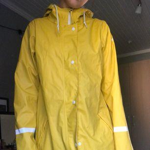 En gul regnjacka i storlek 38, jag har vanligtvis storlek S då jackan sitter perfekt. Passar bra till regniga höst dagar. Kan mötas upp i södra Stockholm annars  frakta då köraren står för kostnaden.