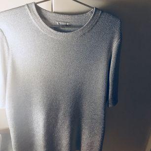 Glittrig grovstickad tröja med kort ärm från COS, otroligt fin på! Helt oanvänd. Storlek L. Slutsåld! Nypris 700 kr.