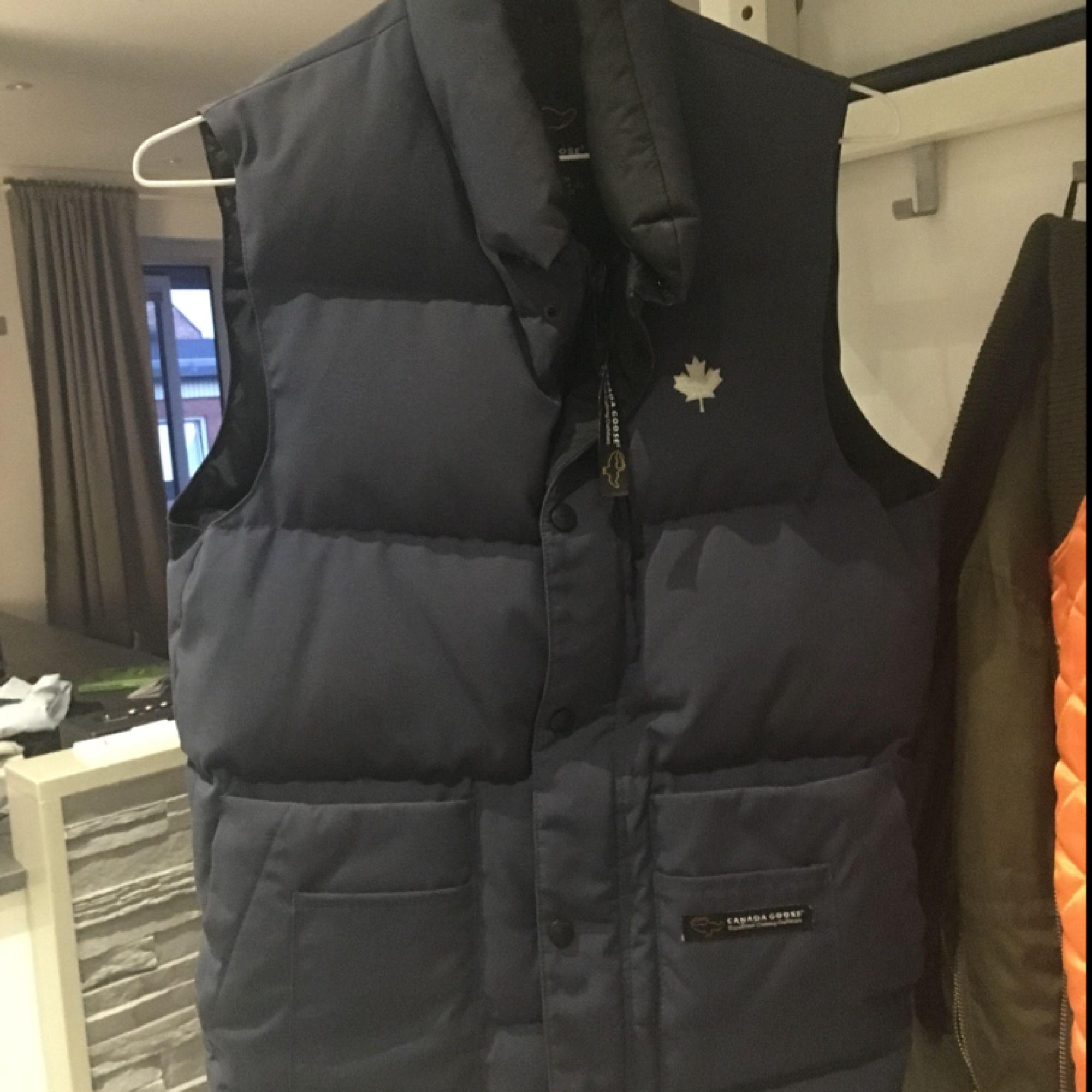 väst i dun från Canadagoose. Har mestadels av sin tid hängt i garderoben då jag användt en likadan fast i svart. Färgen är marinblå,hel och fin utan slitage! Storleken är en 2xs men då den är rymlig i storleken passar den alldeles utmärkt på en s. Jackor.