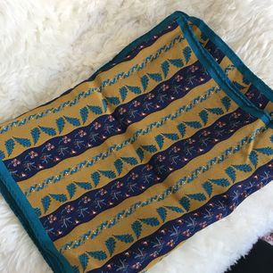 Mönstrad sjal i fina färger (senapsgul, mörkblå och hint av lila och mörkrött). Lite smalare på bredden, men passar utmärkt runt halsen som accessoar eller håret. Priset inkluderar frakt.