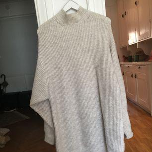 Stickad kofta klänning - dvs oversize stickad tröja som är tänkt som klänning. Den når till ca 10 cm över knäna på mig som är 166cm. I bra skick, använd ca 2 gånger. Skulle påstå att den i princip passar alla storlekar över XXS.