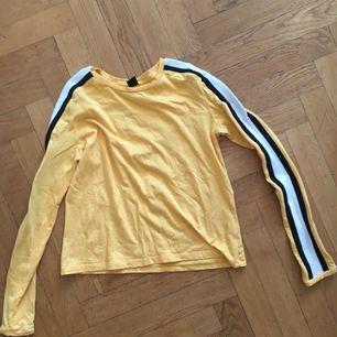 Långärmad tröja/t-shirt köpt på urban outfitters gul med svart o vita ränder på ärmarna. Knappt använd. Tänkt som en kortare tröja men köpte större storlek så att den skulle bli lite längre och inte så tajt