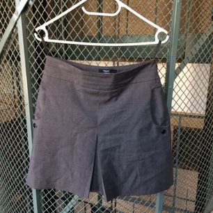 Grå Filippa K kjol, med knapp-detalj och två fickor