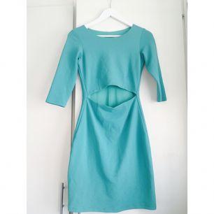 Turkos tajt klänning.