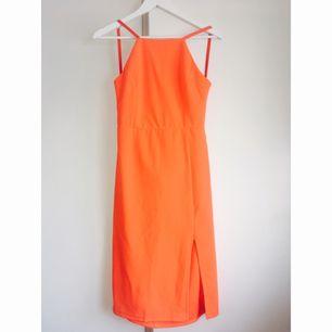 Orange klänning med djup rygg. Liten i storleken.