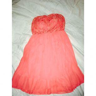 Axelbandslös korallfärgad klänning med spetsdetalj.