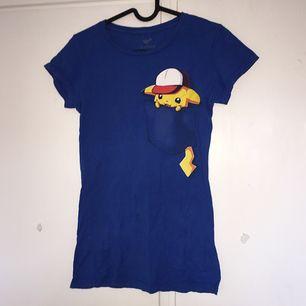 T-shirt med Pikachutryck! Aldrig använd, i nyskick. Skulle eventuellt passa bra att croppas.