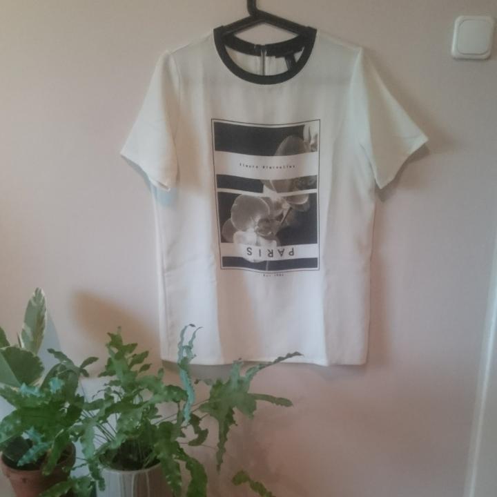 Cool längre T-shirt från Forever 21. Benvit med tryck, kort dragkedja i ryggen och svart krage. Lätt creppat tyg och slutar under rumpan. Fint begagnat skick.  Göteborg/kan skickas. . T-shirts.