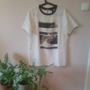 Cool längre T-shirt från Forever 21. Benvit med tryck, kort dragkedja i ryggen och svart krage. Lätt creppat tyg och slutar under rumpan. Fint begagnat skick.  Göteborg/kan skickas.