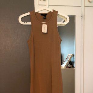 Beige/brun klänning i väldigt skönt material, aldrig använt den. Lappen sitter kvar.