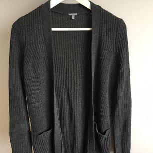 Stickad grå lite längre kofta med två fickor på varje sida. Endast använd ett par gånger, köpt i USA!