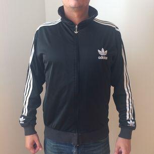 Svart retro jacka från Adidas i fint skick. Betalning via Swish, frakt på 69:- tillkommer.