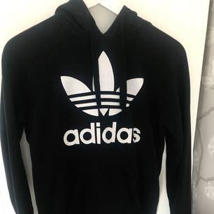 Svart klassisk hoodie från Adidas. Använd men i bra skick. Köparen står för frakt.