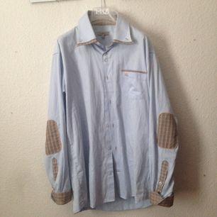 Burberry skjorta. Denna skjorta är äkta, den har en insydd dubbelkrage med burberry mönster på. Armbågslappar med mönster och uppvikta ärmar med mönster på. Priset kan sänkas.