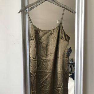 Säljer denna tuffa midiklänning i shimmer-khaki  pga den var för liten. Aldrig använd och tags är kvar! Köpare står för frakt!