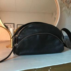 Skitsnygg väska från &otherstories. Har kortat bandet hos en skomakare så bandets längd är 106 cm. Bredd 23 cm och höjd 15 cm. Perfekt liten väska. Äkta läder