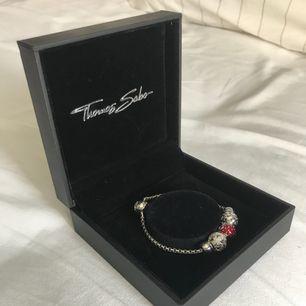 """Thomas Sabo Armband med 3 """"pärlor"""". En liknar en jordgubbe, en har mönster av hjärtan och den sista har mönster av fyrklövrar. De sitter på en kedja som öppnas på andra sidan av pärlorna, fungerar som ett litet lås. Asken följer med i köpet."""