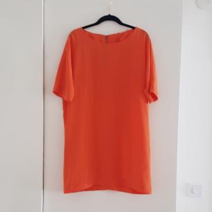 Orange T-shirtklänning i polyester från Ellos. Fint skick.