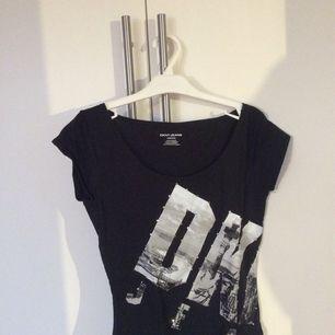 T-shirt med motiv av frihetsgudinnan inköpt på DKNY i San Fransisco. Använd och tvättad, vilket lett till att några stenar fallit av som syns på bild tre.