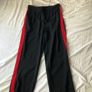 Byxor från Gina Tricot med ett rött streck på sidorna. Helt raka och lösa/pösiga. Fickor i fram. Jag är ca 173cm och är sitter lite längre ner än anklarna. 80kr köparen står för frakt 💞