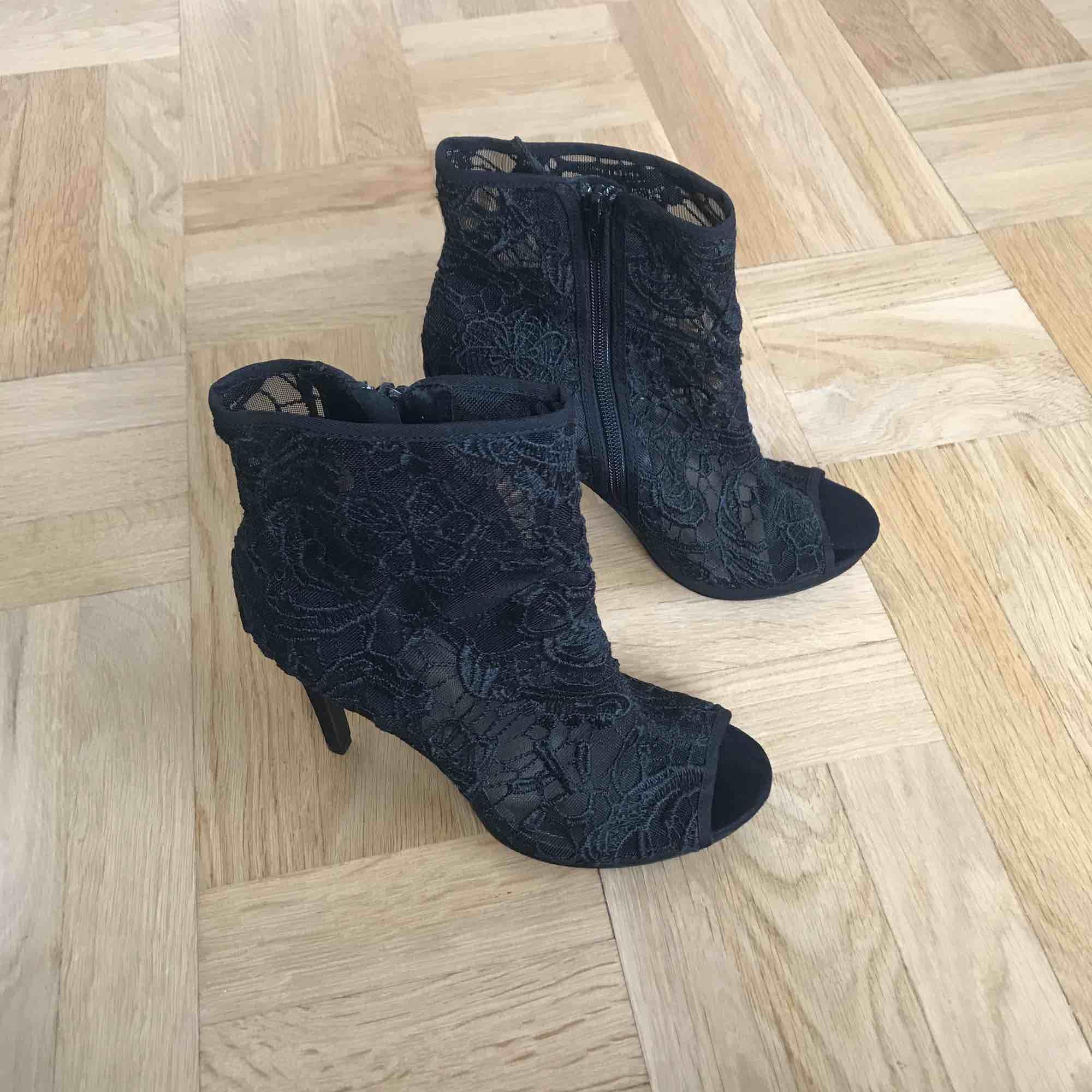 Svarta oanvända klackar i fint mönster! Klackhöjd ca 10 cm. Sååå fina men kommer inte till användning!  Dragkedja på insidan . Skor.