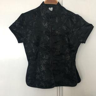 Svart siden blus traditionell kinesisk med ståkrage och fina sydda knappor. Strl s nyskick.