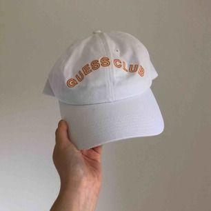 """Vit keps med orange logotyp """"Guess Club"""" från Guess & A$AP Rocky kollektionen. Använd knappast 1 gång. Inkl frakt och kör gärna en meet up i Göteborg."""