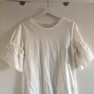 Vit enkel T-shirt med söta detaljer på ärmarna. Endast testad! Nyskick.