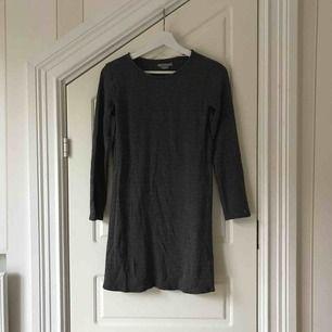 En svart långärmad klänning med vita detaljer