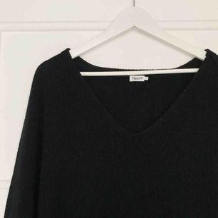 Lång stickad tröja från Filippa K med slits i både ärmslut och sidor. Något nopprig och därav det låga priset