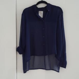 Transparent blå skjorta. Kortare framtill än bak. Mycket fint skick! Som ny