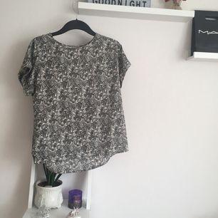Vit/grå mönstrad t-shirt från lager 157 i silkes tyg. säljer pga använder inte ofta så den hänger tyvärr bara i garderoben. tröjan är i strl xs men är mer som en s 🐥köparen står för ev. frakt🦄
