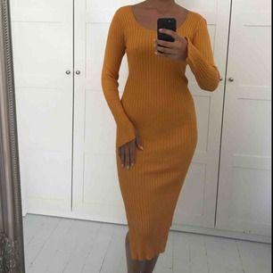 Gul/orange klänning som formar sig efter kroppen med sjuktfina armar