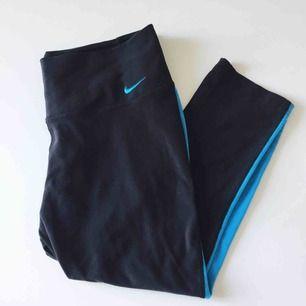 Svarta träningstights med turkosa paneler från Nike. Knappt använda!