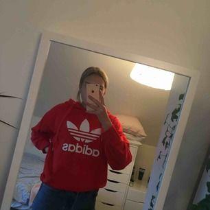 Röd adidas hoodie i jättebra skick!  Köpt i storlek S men skulle säga att den är lite oversized. Frakt är inräknat i priset