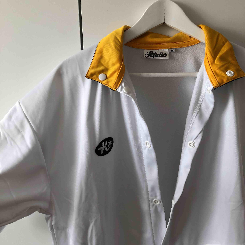 Häftig t-shirt med knappar. Köpt på secondhand. Finns två små fläckar längst ner på t-shirten. Inte vart ett problem för mig då jag stoppat ner den sidan i byxan vid användning. T-shirts.