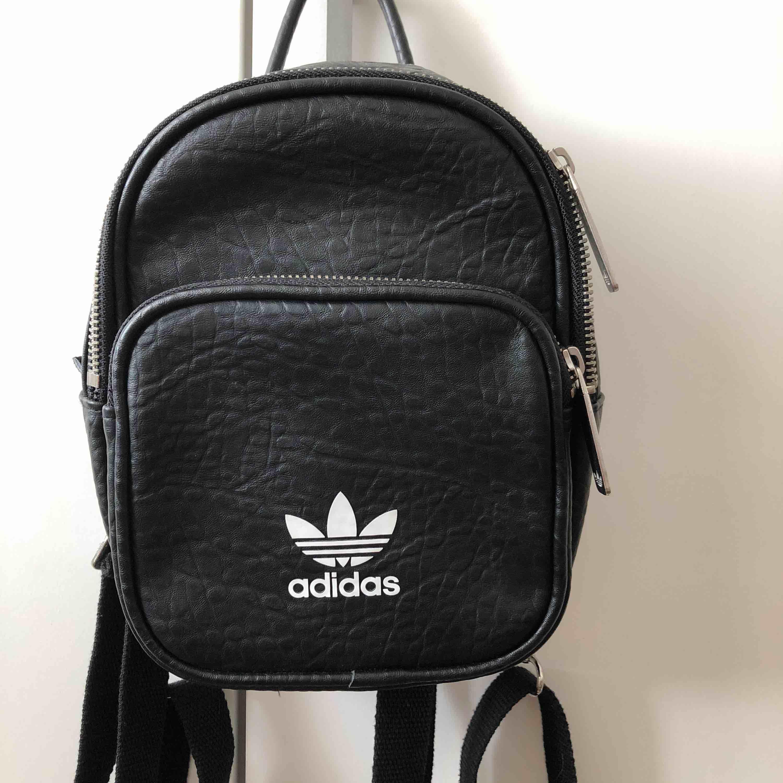 Liten ryggsäck från Adidas. Mycket bra skick. Två fack + ett innerfack. . Väskor.